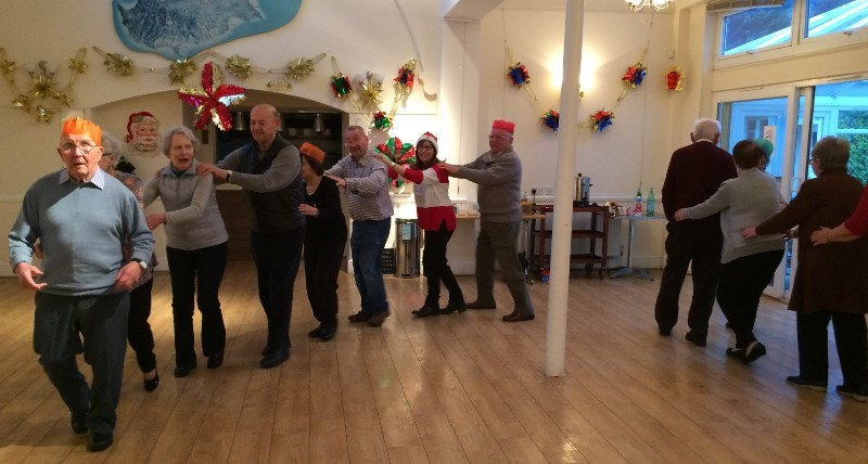 MC leads the conga dance at Dementia Club UK Xmas party 2016