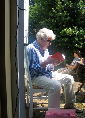 Brian reading in Lisa's garden, with grandson Jason in the background