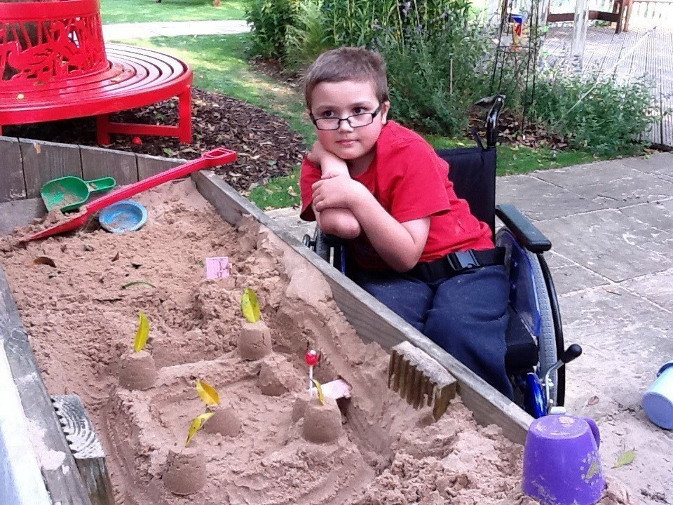 Zak playing in sandpit at Helen House