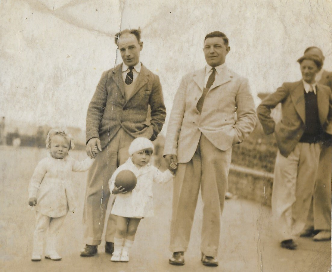 Peter (with the ball and bare legs) and his cousin June (on the left) with their dads.