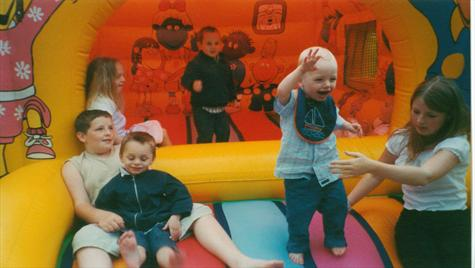 Sam at Aunt Pat's 60th on the bouncy castle with all the kids