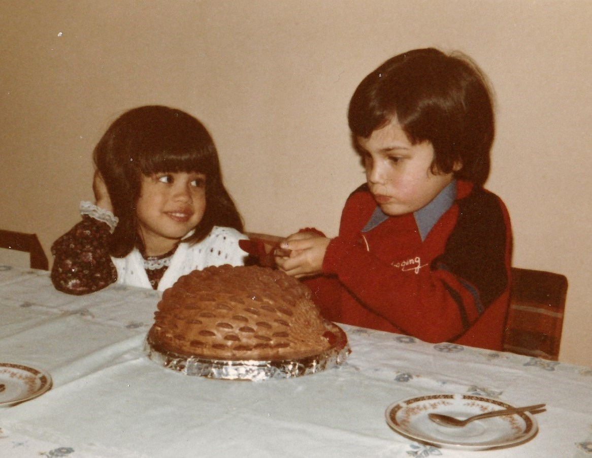 Cutting the birthday cake whilst eliciting much admiration from his sister, Elen