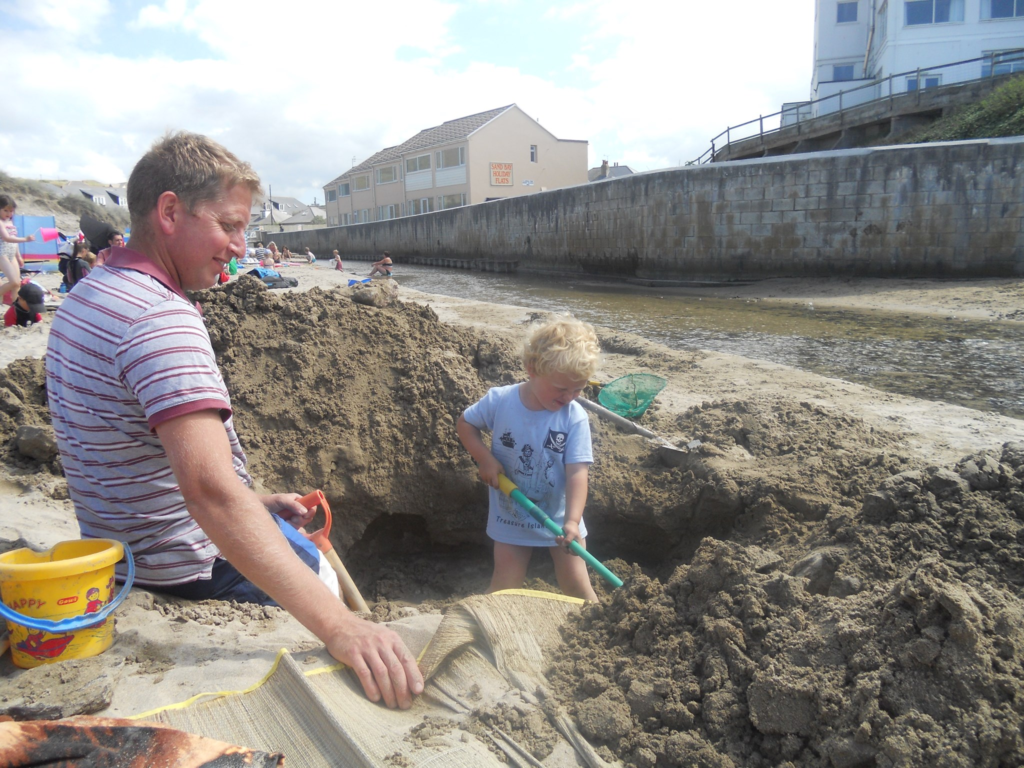 Jack digging a big hole on the beach with Daddy by the stream
