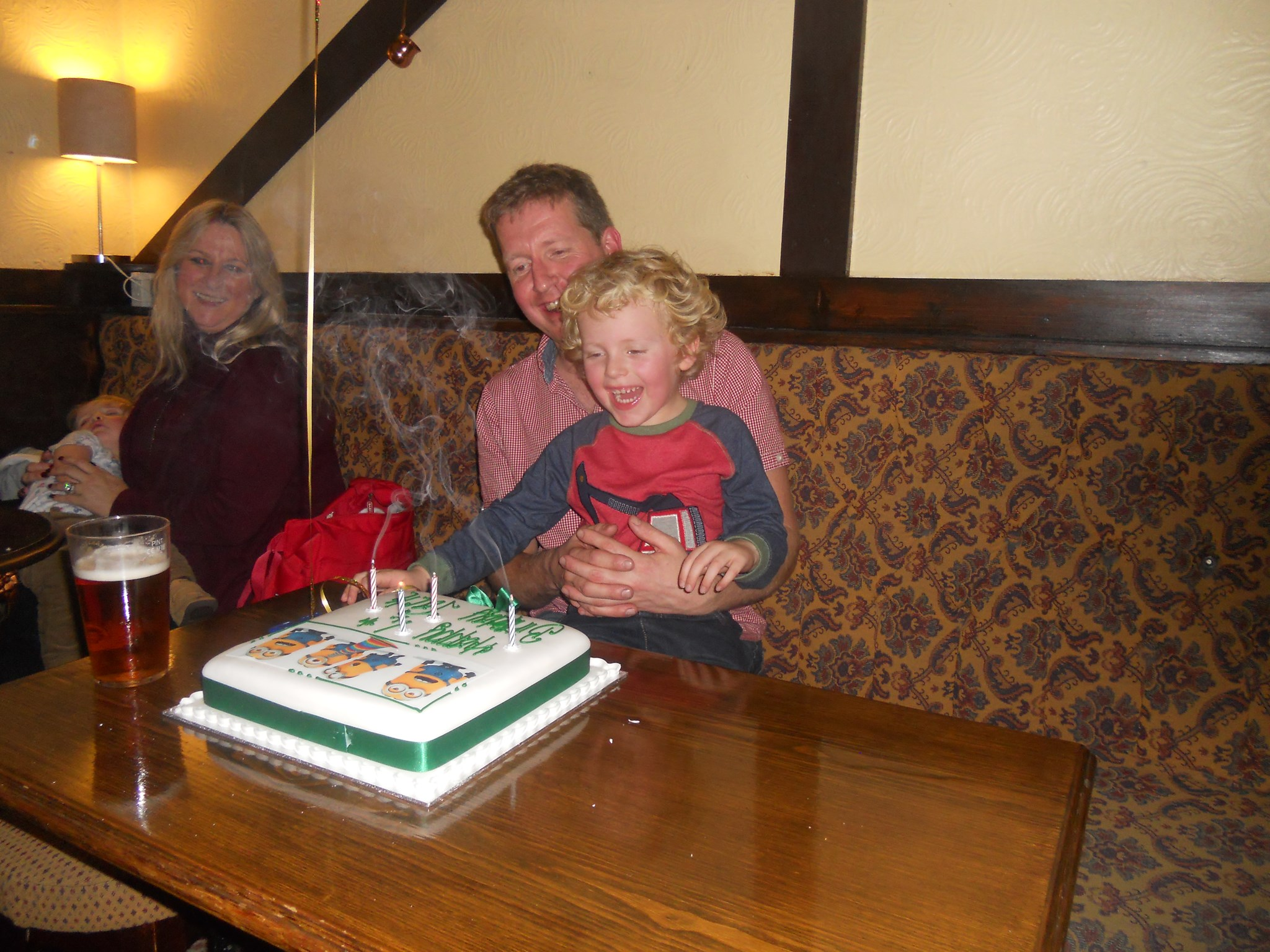 Jack with Daddy blowing his magic candles out on his minion cake at the Anchor