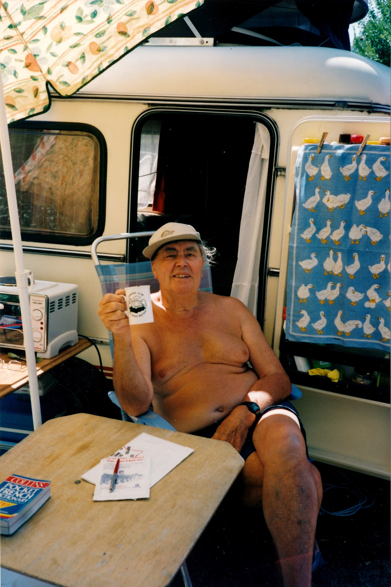 Dad sitting outside caravan with cup of tea