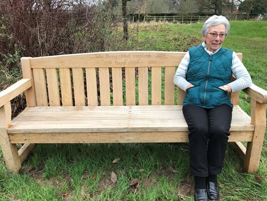 Mum sitting on Dad's memorial bench at Bradfield College Golf Club
