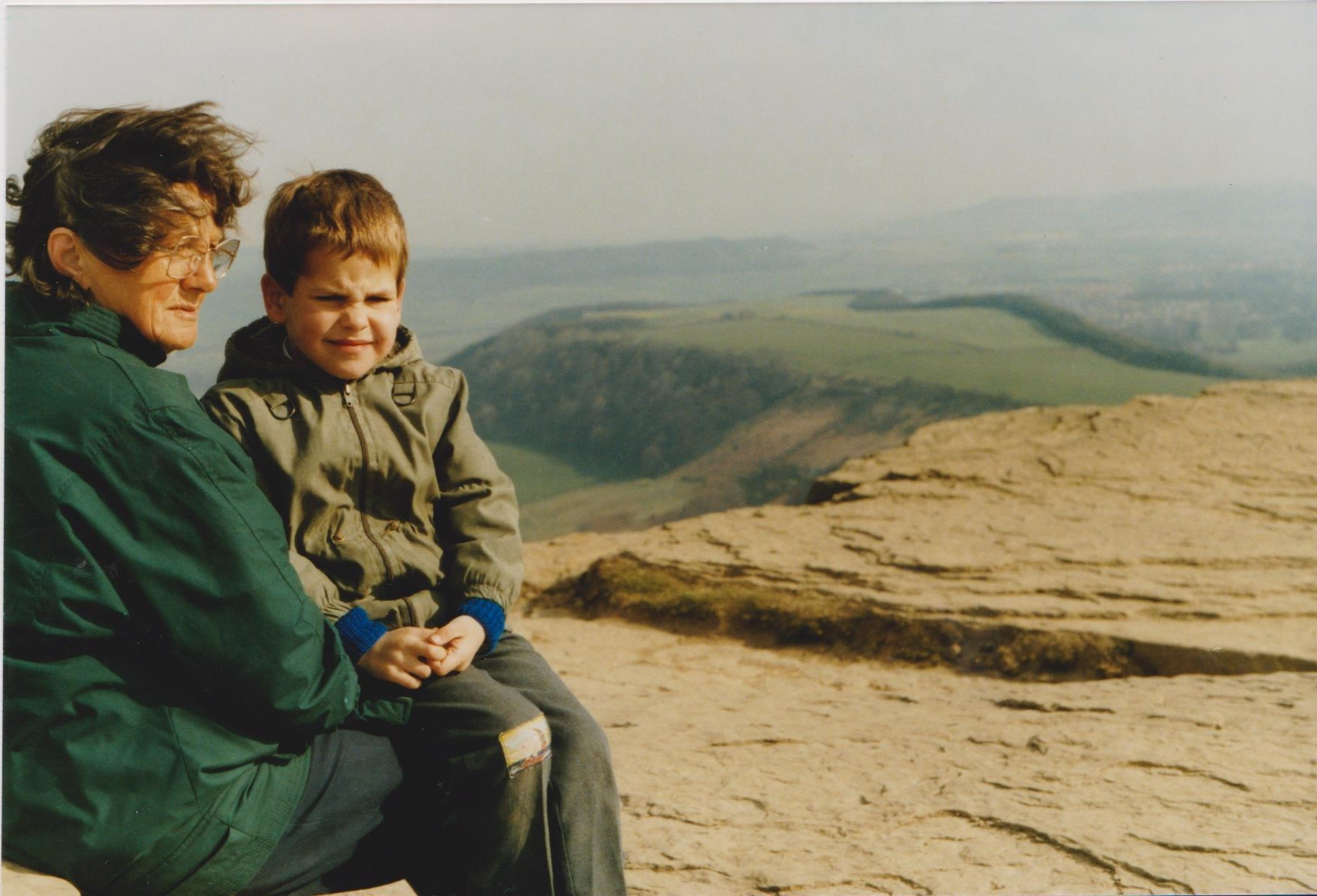 Marco sitting on his Grandmother's knee on top of a hill.